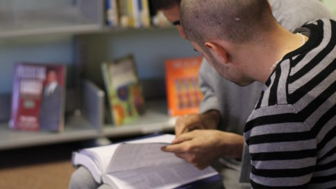 Two young prisoners reading in the library