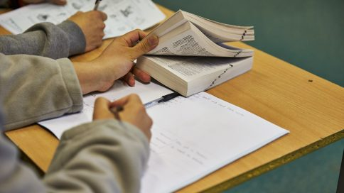 Stock image of a desk with someone using a pad of paper and a textbook